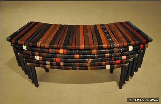 Длинная, изогнутая модульная скамейка обтянута старыми кожаными ремнями...